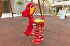 Röd gungbräde i lekplatsen, leksak arkivbild
