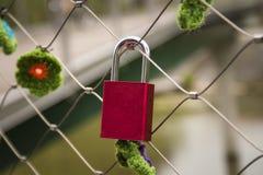 Röd hänglås på en bro arkivfoton