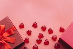 Röd härlig ask med bandet och pilbågen och bredvid en annan röd ask med gåvor på röd bakgrund Närliggande är symboler in Royaltyfri Fotografi