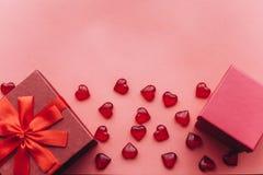 Röd härlig ask med bandet och pilbågen och bredvid en annan röd ask med gåvor på röd bakgrund Närliggande är symboler in Royaltyfria Bilder