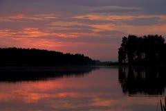 Röd härlig solnedgång i sjön Fotografering för Bildbyråer