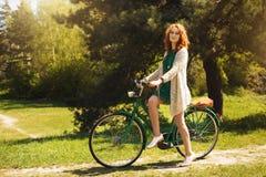 Röd-hår kvinna som rider en cykel Arkivbilder