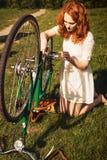 Röd-hår kvinnareparation en cykel Fotografering för Bildbyråer