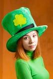Röd hårflicka i Sts Patrick hatt för dagparti Arkivfoton