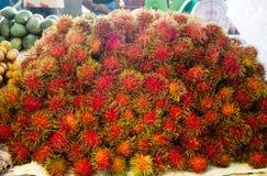 Röd hårig och taggig rambutan, typ av tropiska nya frukter fotografering för bildbyråer