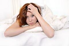 Röd hårkvinna på säng som vaknar upp med bakrus och huvudvärk Arkivfoton