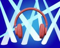 Röd hörlurar på blåttstrålkastare Arkivbild