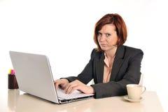 Röd haired kvinna för uttråkad affär i spänning på arbete med bärbara datorn Arkivfoto
