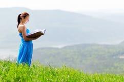 Röd haired kvinna med boken på bergstoppet Arkivfoton