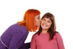 Röd haired kvinna som kysser hennes dotter Royaltyfria Bilder