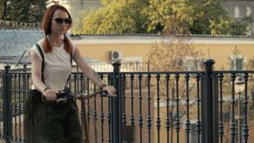 Röd haired kvinna som rider upp en cykel på stadsbakgrundsslut Kvinnacykelstad arkivfilmer