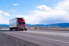 Röd halv lastbil för stor rigg med kyld halv släptransporti Royaltyfri Bild