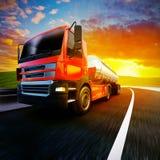 Röd halv lastbil på den oskarpa asfaltvägen under aftonhimmel och solar Arkivbilder