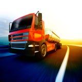 Röd halv lastbil på den oskarpa asfaltvägen under aftonhimmel och solar Fotografering för Bildbyråer