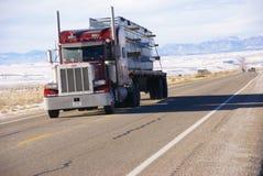 Röd halv lastbil på vintervägen Arkivbild
