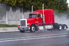 Röd halv lastbilrigg med den långa taxin på att regna huvudvägen Royaltyfria Bilder