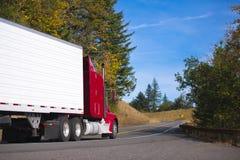 Röd halv lastbilrigg och släp på den convoluted huvudvägen för höst Arkivbild