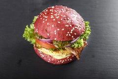 Röd hamburgare på tabellen arkivbild