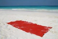 Röd handduk på den härliga stranden Arkivbild