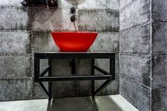 Röd handfat med vattenkranen i dyrt vindbadrum i elitsportstång på svart bakgrund för tegelstenvägg arkivfoton