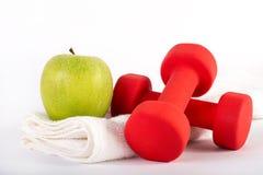Röd hantel och grönt nytt äpple på handduken på vit bakgrund i studio Arkivfoton
