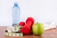 Röd hantel på handduken, det gröna nya äpplet och flaskan med vatten och mätabandet på trägolv Royaltyfri Bild