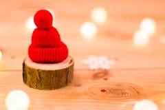 Röd hatt på ett stycke av trä med ljus och en snöflinga royaltyfria bilder