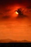 Röd himmel med svarta byggnader Arkivbild