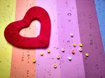 Röd hjärta av tråden på en kulör bakgrund royaltyfri foto