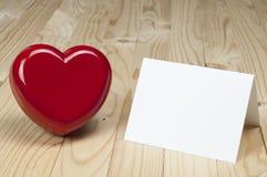 Röd hjärta bredvid det vita tomma kortet Arkivbild