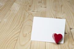 Röd hjärta bredvid det vita tomma kortet Arkivfoto