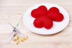 Röd hjärta för begrepp på plattan med injektionssprutan och stimulans på trä b royaltyfri bild