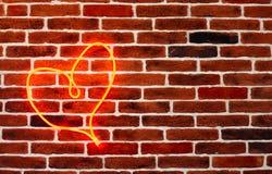 R?d hj?rta f?r neon p? tegelstenv?ggen Romantisk grungebakgrund arkivfoto