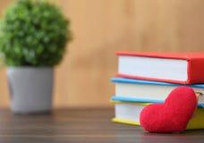 Röd hjärta för valentindag med färgrika böcker på gammalt trä holida Arkivbild