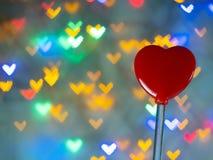 Röd hjärta formade leksaken på många bakgrundsbokehhjärtor arkivfoto