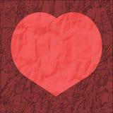 Röd hjärta från skrynkligt papper på en burgundy bakgrund royaltyfria foton