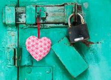 Röd hjärta hänger på en dörr med låset Royaltyfri Fotografi