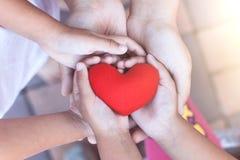 Röd hjärta i barn- och förälderhänder med förälskelse och harmoni royaltyfria foton