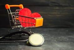 Röd hjärta i en supermarketspårvagn och stetoskop Begreppet av medicin och sjukförsäkring, familj, liv ambulant Cardiol arkivfoton