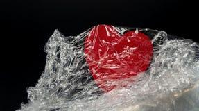 Röd hjärta i filmen på en svart bakgrundsnärbild arkivfoton