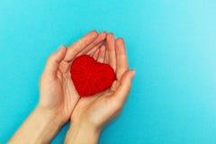 Röd hjärta i händer på en blå bakgrund royaltyfri bild