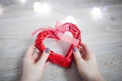 Röd hjärta i händerna av en ung kvinna Royaltyfri Fotografi