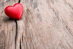 Röd hjärta i spricka av träplankan Arkivbild