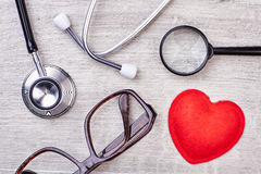 Röd hjärta, loupe och stetoskop Royaltyfri Foto