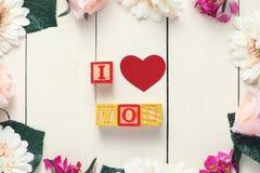 Röd hjärta med ÄLSKAR JAG DIG i kub på den wood tabellen Royaltyfri Foto