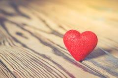 Röd hjärta med blänker på trä Royaltyfria Bilder