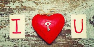 Röd hjärta med en liten metalltangent- och korttext ÄLSKAR JAG DIG Arkivbild