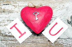 Röd hjärta med en liten metalltangent- och korttext ÄLSKAR JAG DIG Royaltyfri Bild