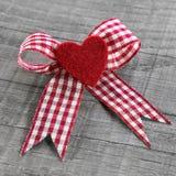 Röd hjärta med en röd vit kontrollerade bandet för valentindag. Fotografering för Bildbyråer