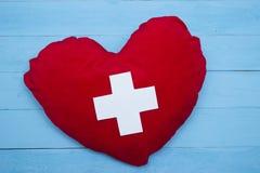 Röd hjärta med ett vitt kors på blå bakgrund Royaltyfria Bilder